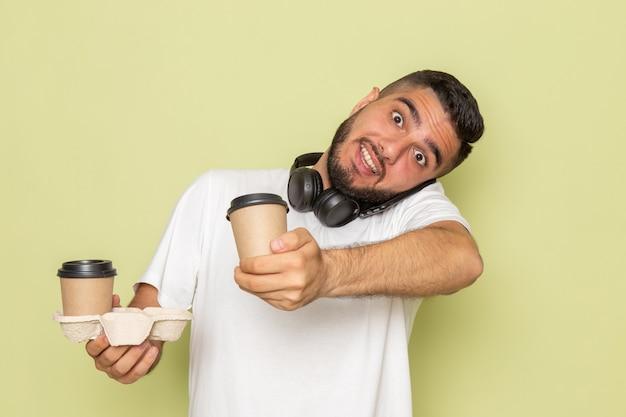 Un giovane maschio di vista frontale in maglietta bianca che tiene le tazze di caffè e che parla sul telefono