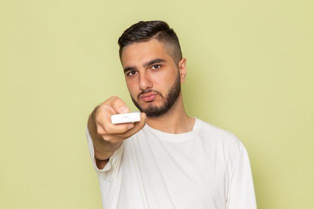Un giovane maschio di vista frontale in maglietta bianca che tiene telecomando