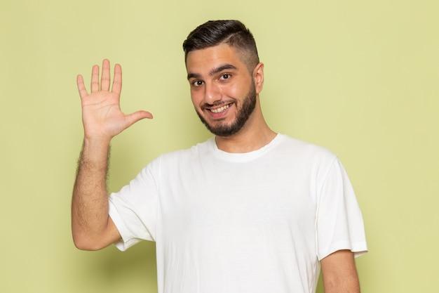 Un giovane maschio di vista frontale in maglietta bianca saluta e sorride