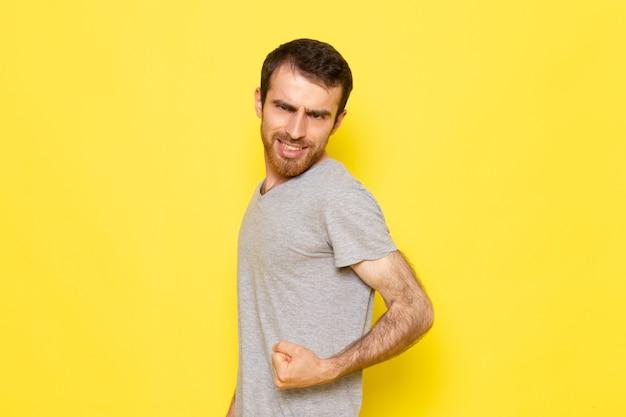 Un giovane maschio di vista frontale in maglietta grigia che flette sul modello di colore di emozione di espressione dell'uomo della parete gialla