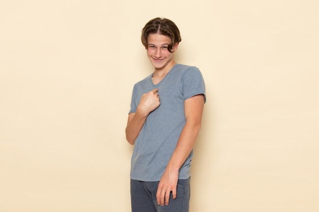 Un giovane maschio di vista frontale in maglietta grigia che posa con il sorriso