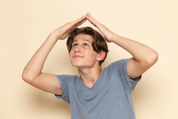 Un giovane maschio di vista frontale in maglietta grigia che posa sorridente e che forma casa sopra la sua testa