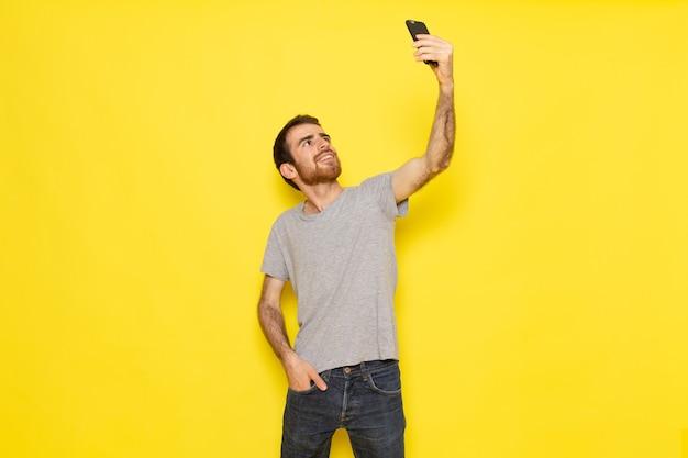 Un giovane maschio di vista frontale in maglietta grigia che prende un selfie sui vestiti gialli di emozione del modello di colore dell'uomo della parete