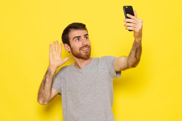 Un giovane maschio di vista frontale in maglietta grigia che prende un selfie sul modello di colore di emozione di espressione dell'uomo della parete gialla