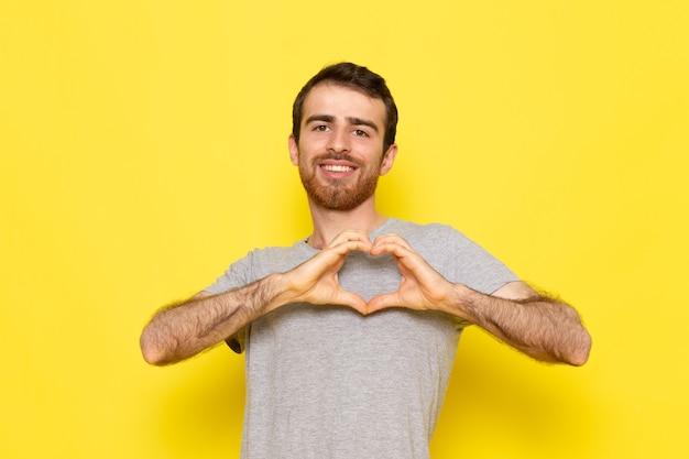 Un giovane maschio di vista frontale in maglietta grigia che sorride e che mostra il segno di amore sui vestiti gialli di emozione del modello di colore dell'uomo della parete