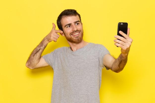 Un giovane maschio di vista frontale in maglietta grigia che sorride e che prende un selfie sui vestiti gialli di emozione del modello di colore dell'uomo della parete