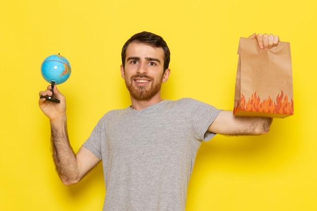 Un giovane maschio di vista frontale in maglietta grigia che tiene il pacchetto dell'alimento e piccolo globo sui vestiti gialli di emozione del modello di colore dell'uomo della parete