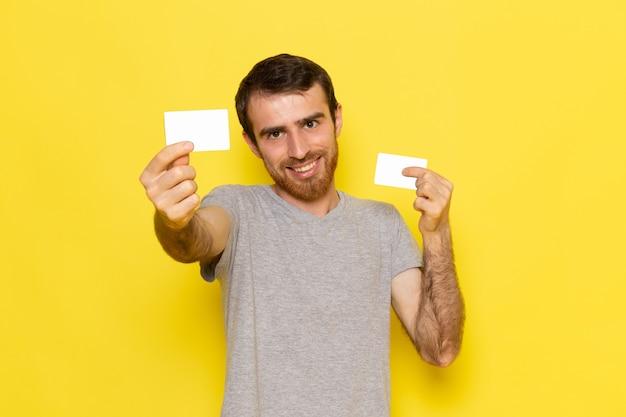 Un giovane maschio di vista frontale in maglietta grigia che tiene le carte bianche sul modello di colore di emozione di espressione dell'uomo della parete gialla