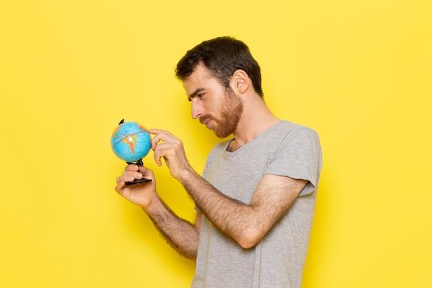 Un giovane maschio di vista frontale in maglietta grigia che tiene piccolo globo sui vestiti gialli di emozione del modello di colore dell'uomo della parete