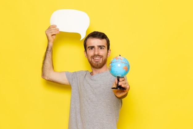 Un giovane maschio di vista frontale in maglietta grigia che tiene segno bianco e piccolo globo sui vestiti gialli di emozione del modello di colore dell'uomo della parete