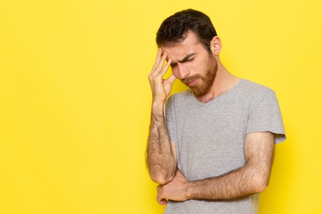 Un giovane maschio di vista frontale in maglietta grigia con l'espressione di pensiero sul colore giallo di emozione di espressione dell'uomo della parete