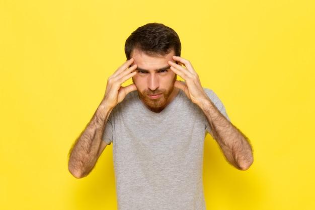 Un giovane maschio di vista frontale in maglietta grigia con l'espressione di pensiero sul modello di colore di espressione dell'uomo della parete gialla