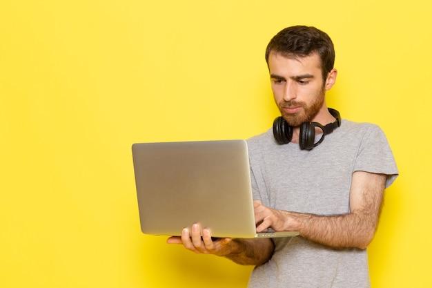 Un giovane maschio di vista frontale in maglietta grigia facendo uso del computer portatile sul modello di colore di colore di emozione di espressione dell'uomo della parete gialla