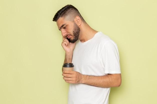 Un giovane maschio di vista frontale in t-shirt bianca che tiene tazza di caffè e parla al telefono
