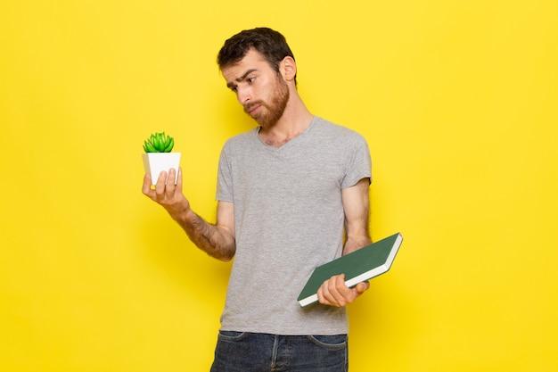 Un giovane maschio di vista frontale in t-shirt grigia che tiene il quaderno e pianta sul modello di colore di emozione di espressione dell'uomo della parete gialla