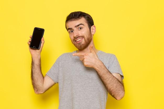 Un giovane maschio di vista frontale in t-shirt grigia che tiene smartphone con il sorriso sul modello di colore di emozione di espressione dell'uomo della parete gialla