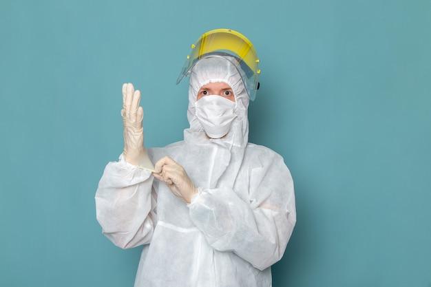Un giovane maschio di vista frontale in vestito speciale bianco e casco speciale giallo che indossa guanti bianchi sul colore dell'attrezzatura speciale del pericolo del vestito dell'uomo della parete blu