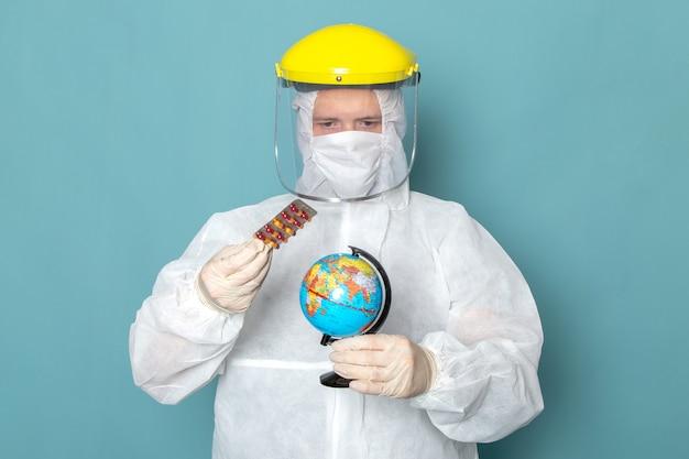 Un giovane maschio di vista frontale in vestito speciale bianco e casco speciale giallo che tiene piccolo globo e pillole sul colore speciale del pericolo del vestito dell'uomo della parete blu