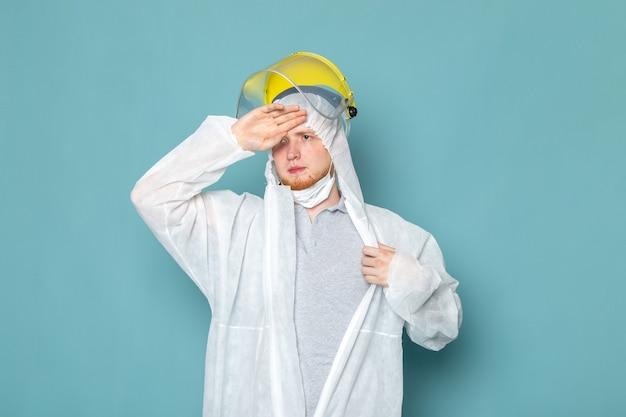 Un giovane maschio di vista frontale in vestito speciale bianco e casco speciale giallo sul colore dell'attrezzatura speciale del pericolo del vestito dell'uomo della parete blu