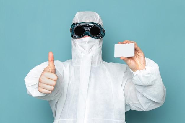 Un giovane maschio di vista frontale in vestito speciale bianco e che tiene carta bianca sul colore dell'attrezzatura speciale del pericolo del vestito dell'uomo della parete blu