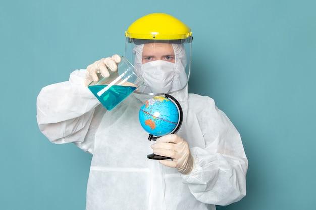 Un giovane maschio di vista frontale in vestito speciale bianco e globo speciale giallo della tenuta del casco sul colore blu dell'attrezzatura speciale del pericolo del vestito dell'uomo della parete
