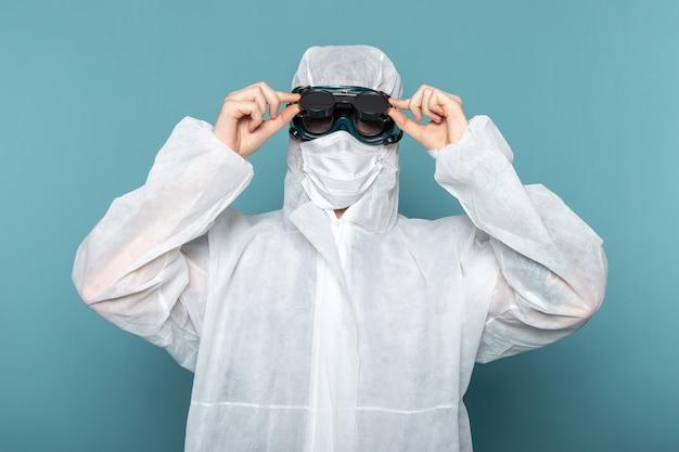 Un giovane maschio di vista frontale in vestito speciale bianco e occhiali da sole protettivi unici sul colore dell'attrezzatura speciale del pericolo del vestito dell'uomo della parete blu