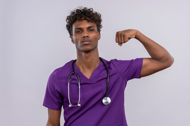 Un giovane medico dalla carnagione scura bello aggressivo con capelli ricci che portano l'uniforme viola con lo stetoscopio che alza il pugno chiuso