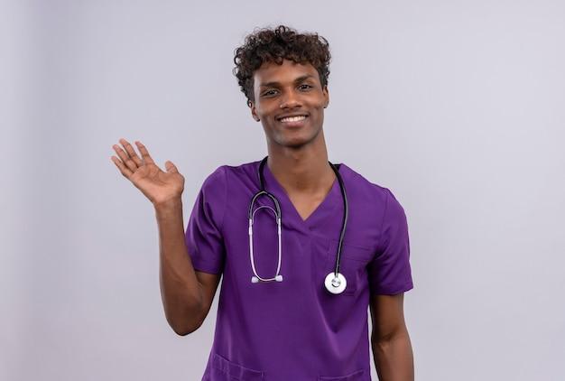 Un giovane medico dalla carnagione scura bello con capelli ricci che porta l'uniforme viola con lo stetoscopio che mostra arrivederci