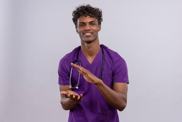 Un giovane medico dalla carnagione scura bello con capelli ricci che porta l'uniforme viola con lo stetoscopio che prepara ad battere le mani
