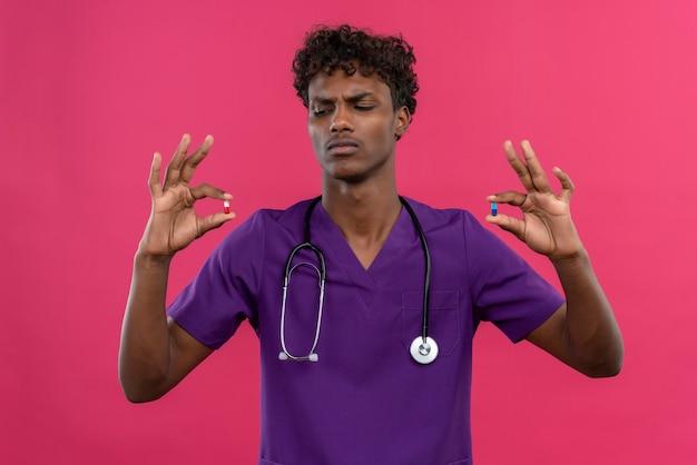 Un giovane medico dalla carnagione scura bello serio con capelli ricci che porta l'uniforme viola con lo stetoscopio che esamina le pillole