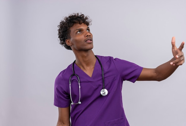 Un giovane medico dalla carnagione scura bello sicuro con capelli ricci che porta l'uniforme viola con lo stetoscopio che guarda verso l'alto mentre solleva le mani