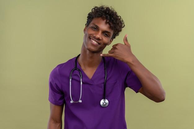 Un giovane medico dalla carnagione scura bello sorridente con capelli ricci che indossa l'uniforme viola con lo stetoscopio che tiene la mano vicino al segno del telefono di gesto dell'orecchio con le dita su uno spazio verde