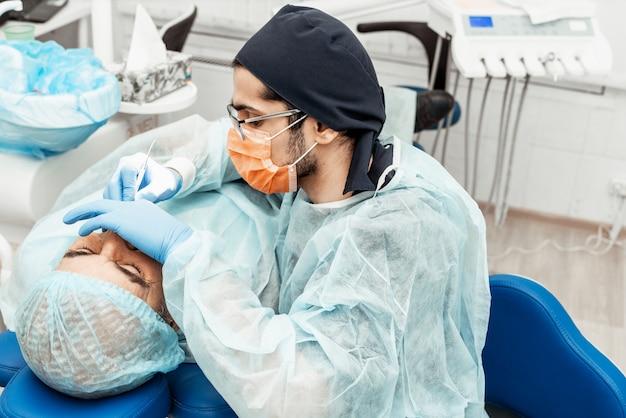 Un giovane medico dentista maschio tratta un paziente. manipolazioni mediche in odontoiatria, chirurgia. uniforme professionale e attrezzature di un dentista. assistenza sanitaria equipaggia il posto di lavoro di un medico. odontoiatria