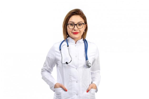 Un giovane medico femminile di vista frontale in vestito medico bianco con lo stetoscopio che sorride sul bianco