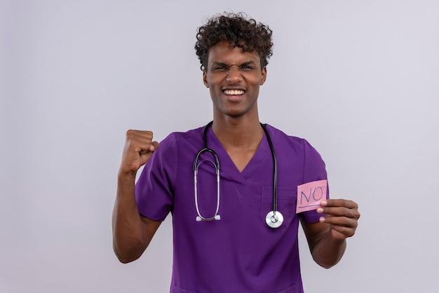 Un giovane medico maschio dalla carnagione scura bello con capelli ricci che indossa l'uniforme viola con uno stetoscopio che mostra una scheda di carta con la parola no con il pugno chiuso