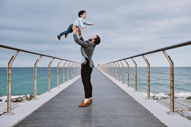 Un giovane padre su un ponte con suo figlio che vola sopra di lui