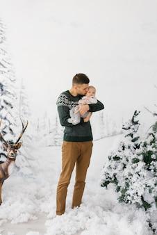 Un giovane papà tiene in braccio un figlio neonato in una zona fotografica in stile foresta invernale con un cervo e papà bacia suo figlio