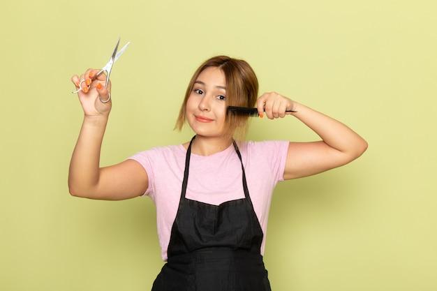 Un giovane parrucchiere femminile di vista frontale in maglietta rosa e mantello nero che tiene la spazzola e le forbici che riparano i suoi capelli che sorridono sul verde
