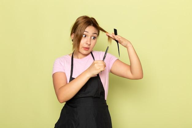 Un giovane parrucchiere femminile di vista frontale in maglietta rosa e mantello nero che tiene la spazzola e le forbici che riparano i suoi capelli sul verde