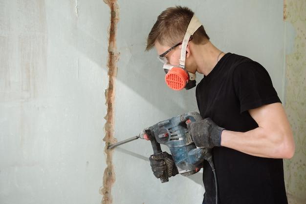 Un giovane perfora un muro con un perforatore