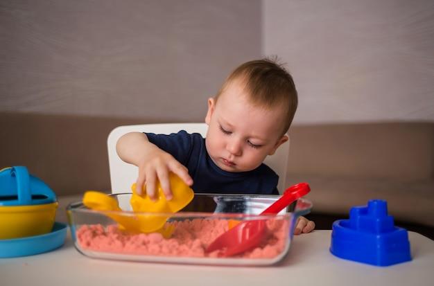 Un giovane ragazzo carino gioca in una sandbox domestica e crea forme dalla sabbia.