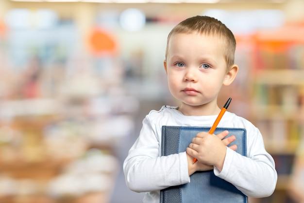 Un giovane ragazzo di scuola tiene in mano un libro blu