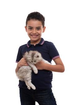 Un giovane ragazzo felice che sorride con il gattino simile a pelliccia su fondo bianco