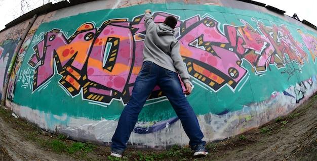 Un giovane ragazzo in una felpa grigia dipinge graffiti in rosa e verde c