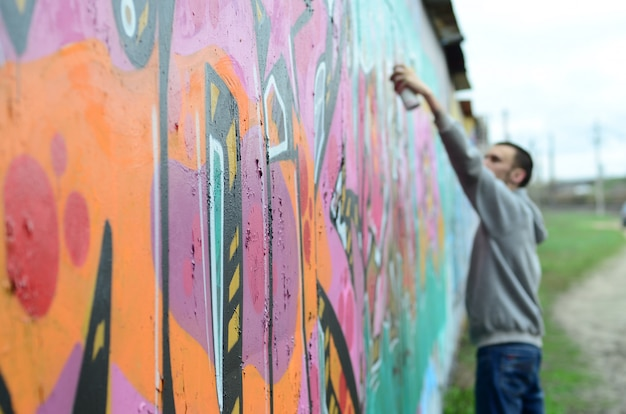 Un giovane ragazzo in una felpa grigia dipinge graffiti in rosa e verde
