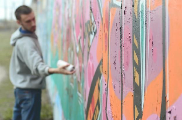Un giovane ragazzo in una felpa grigia dipinge graffiti