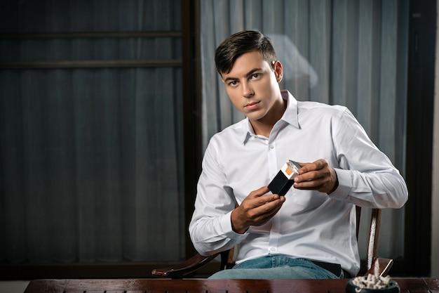 Un giovane ragazzo pone seduto a un tavolo su cui si trova un posacenere pieno di sigarette
