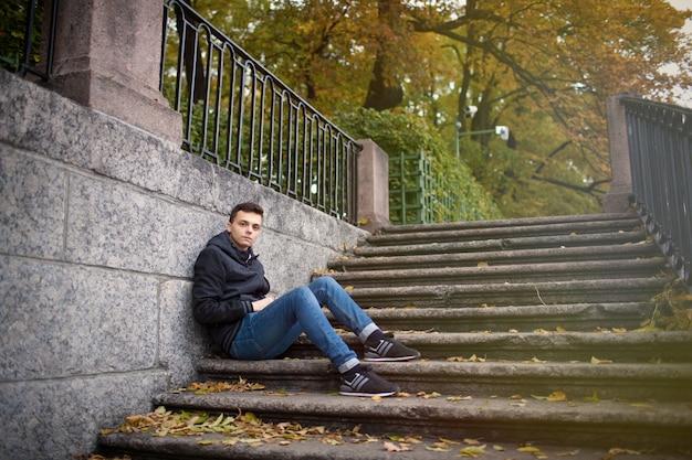 Un giovane ragazzo seduto sulle scale.
