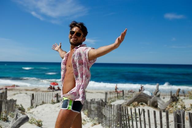 Un giovane sexy felice in posa con le mani alzate sulla spiaggia, vestito con un costume da bagno e una camicia estiva, isolato sulla spiaggia, sullo sfondo dell'oceano. vista orizzontale corsica, francia.