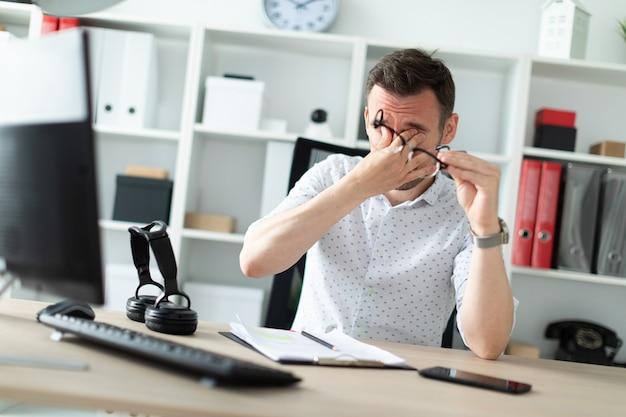 Un giovane si siede a un tavolo in ufficio, si tolse gli occhiali e si stropicciò gli occhi.